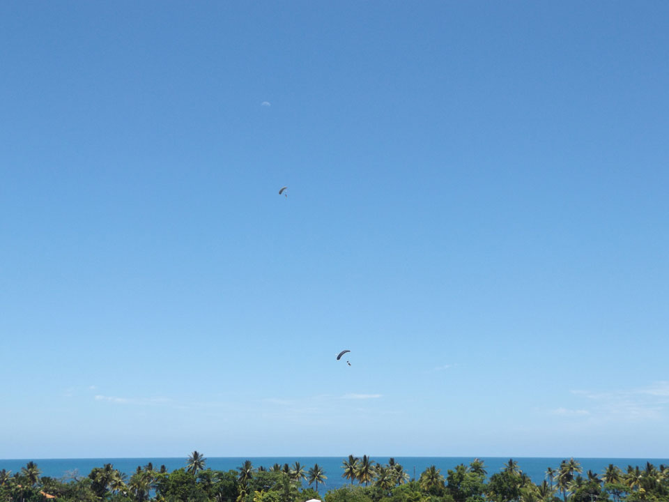 Skydivers Landing on the beach at Mission Beach with the moon visible